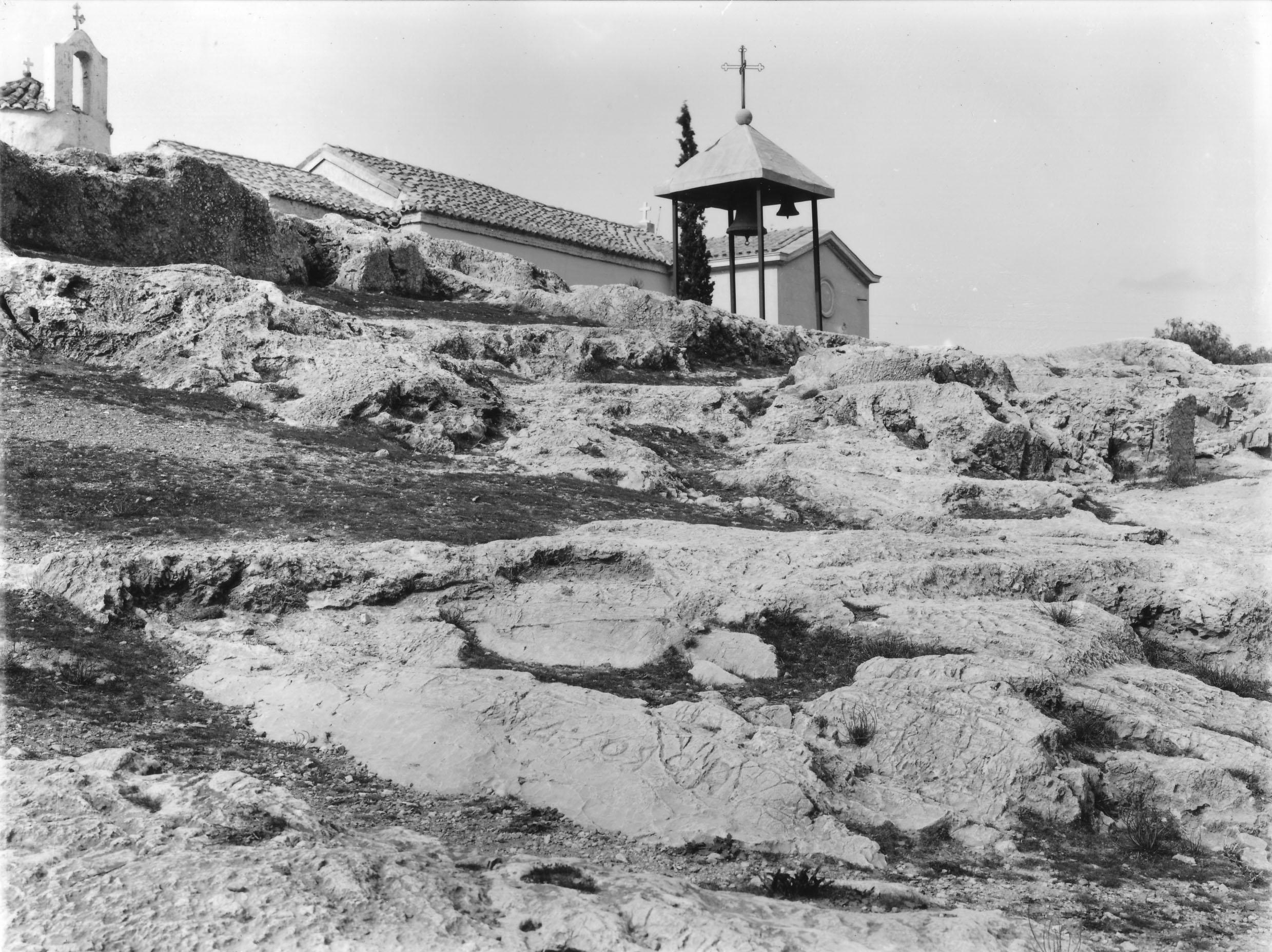 Σε πρώτο πλάνο, υπαίθριο αρχαϊκό ιερό αφιερωμένο στο Δία εντοπίζεται από επιγραφή λαξευμένη με αντίστροφη γραφή: HΟΡΟΣ ΔΙΟΣ (6ος αι. π.Χ.) (Nicholson Museum, Professor W.J. Woodhouse Collection).