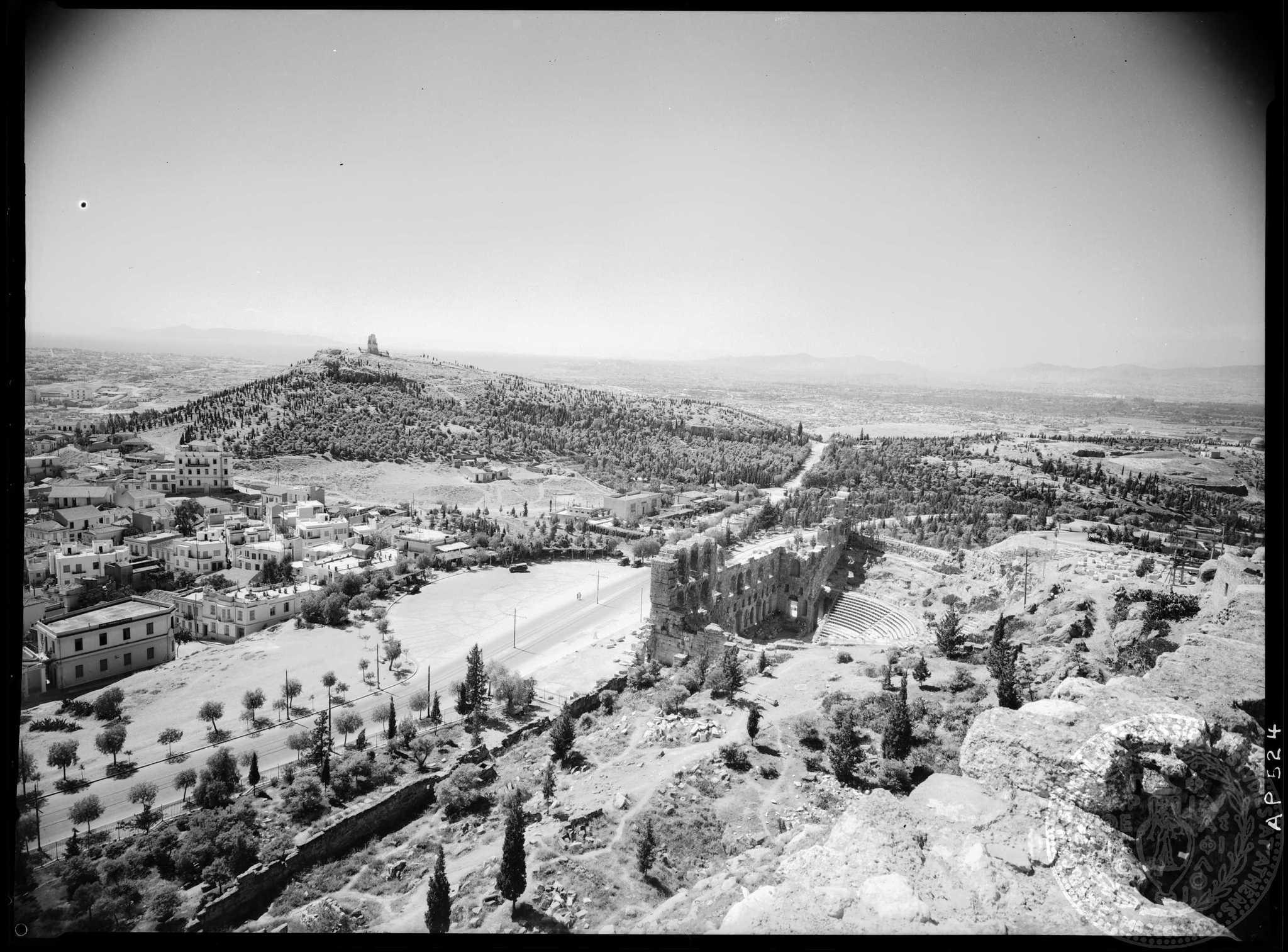 Η δενδροφύτευση στον λόφο των Μουσών (Φιλοπάππου) έχει ήδη καλύψει ένα μεγάλο τμήμα του λόφου· αριστερά, πίσω από τα σπίτια, το οικοδομικό τρίγωνο παραμένει ακόμα άκτιστο (Αμερικανική Σχολή Κλασικών Σπουδών στην Αθήνα, Αρχαιολογικό Φωτογραφικό Αρχείο, AP 0524).