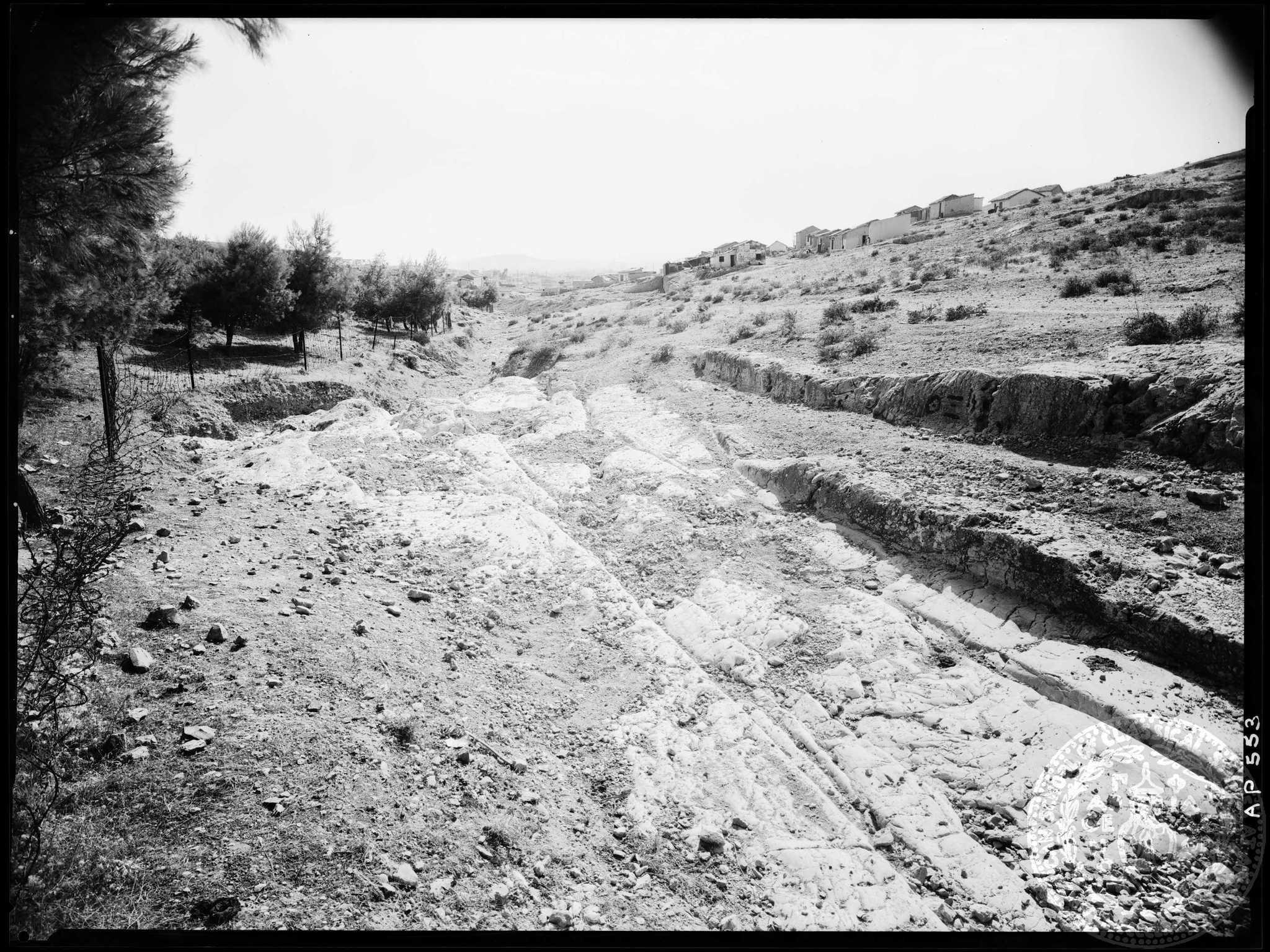 Το βλέμμα ανηφορίζει στα σπιτάκια του Ασυρμάτου, πέρα από τον δρόμο με τις αρχαίες αρματροχιές (Αμερικανική Σχολή Κλασικών Σπουδών στην Αθήνα, Αρχαιολογικό Φωτογραφικό Αρχείο, AP 0553).